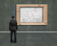 Businessman looking at business doodles drawn on white board ind Royalty Free Stock Image