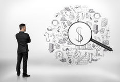 Businessman looking at business doodles through a magnifier and seeing dollar sign. Back view of a businessman looking at business doodles through a magnifier royalty free stock images
