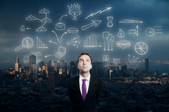 Businessman looking at business sketch. Businessman looking up at abstract business sketch on city background Royalty Free Stock Photos
