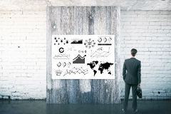 Businessman looking business sketch on the wall Royalty Free Stock Photo