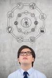 Businessman looking at business symbols Stock Photos