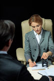 Businessman looking at businesswoman signing and stamping papers royalty free stock images