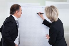 Businessman looking at businesswoman writing on flipchart Royalty Free Stock Photo