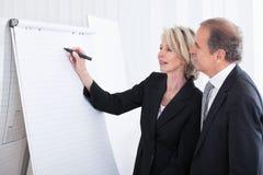Businessman looking at businesswoman writing on flipchart Stock Photo