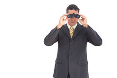 Businessman looking at the camera with binoculars Royalty Free Stock Photography