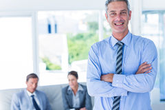 Businessman looking at camera with his colleagues behind him Stock Photos
