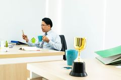 Businessman looking cell phone. Businessman looking at cell phone while holding a cup of coffee stock photo