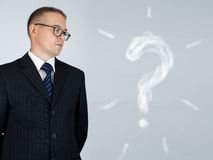 Businessman is looking at chalk drawn question mark Royalty Free Stock Photos