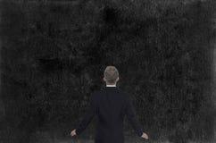 Businessman Looking at Chalkboard Wall Stock Photo