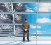 Businessman looking at changing weather Royalty Free Stock Images