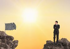 Businessman looking at checkered flag while standing on rocks against sky. Digital composite of Businessman looking at checkered flag while standing on rocks Stock Photo