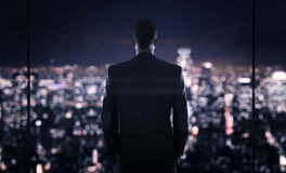 Businessman looking at the the city. Close up of young successful businessman looking at the the city at night Royalty Free Stock Photo