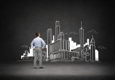 Businessman looking at city drawing. Business, people, development and architecture concept - businessman looking at city drawing over concrete room background Royalty Free Stock Photography