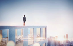 Businessman looking at city in sunrise. 3d Stock Photography
