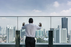 Businessman looking at the city view from the top of a building Stock Photography