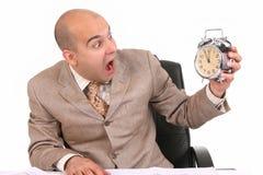 Businessman looking at clock alarm stock image