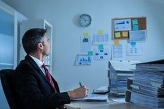 Businessman looking at clock Stock Photo