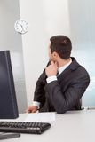 Businessman looking at clock at the office stock photos