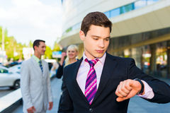 Businessman looking clock. Young businessman looking clock on modern building background Stock Photography
