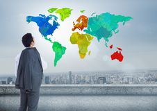 Businessman looking at Colorful Map with city background. Digital composite of Businessman looking at Colorful Map with city background Royalty Free Stock Photo