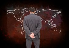 Businessman looking at Colorful Map with paint splatters on wall background Royalty Free Stock Photos