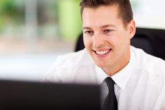 Businessman looking computer. Handsome businessman looking at computer screen at workplace Stock Images
