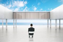 Businessman looking at concrete building. Sitting businessman looking at concrete exterior by the sea on bright blue sky background. 3D Rendering Royalty Free Stock Photos