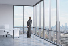 Businessman is looking through the corner window. New York background. Royalty Free Stock Photo