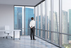 Businessman is looking through the corner window. Singapore background. Royalty Free Stock Photos