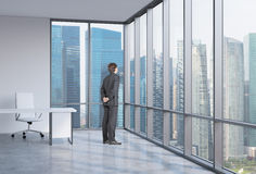 Businessman is looking through the corner window. Singapore background. Royalty Free Stock Photography