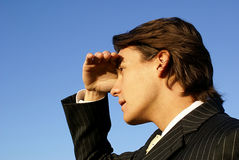 Businessman looking into the d. Man in business suit shielding his eyes looking into the horizon Royalty Free Stock Photo