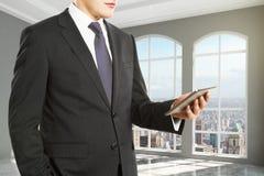 Businessman looking at digital tablet in empty loft room Stock Photos
