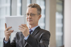 Businessman looking at digital tablet in office Stock Photo