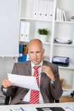 Businessman Looking At Document At Desk Royalty Free Stock Photos