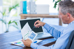 Businessman looking at documents with graphic Stock Photography