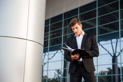 Businessman looking through documents while standing outdoors at the office Stock Images