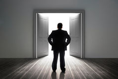 Businessman looking at door showing bright light. In dull grey room Royalty Free Stock Photography