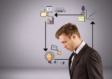 Businessman looking down with arrows and business graphic drawings Stock Images