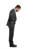 Businessman looking down. Full length portrait of thinking businessman looking down. isolated on white background Stock Photography