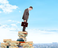 Businessman looking down from piles of books Stock Photo
