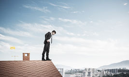 Businessman looking down from roof and afraid to make step. Mixe Stock Photo