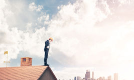 Businessman looking down from roof and modern cityscape at backg Royalty Free Stock Image