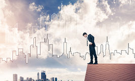 Businessman looking down from roof and modern cityscape at backg Stock Photos