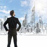 Businessman looking at drawn city. Back view of thoughtful young businessman looking at drawn city on blue sky background stock photos