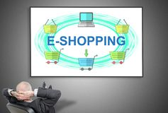 Businessman looking at e-shopping concept. Relaxed businessman looking at e-shopping concept on a whiteboard royalty free stock photos