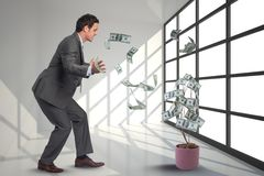 Businessman is looking at falling money from a tree against office background. Digital composite of business models with falling money Royalty Free Stock Photo