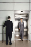 Businessman Looking At Female Colleague Exiting Elevator. Rear view of businessman looking at female colleague exiting elevator in office royalty free stock images