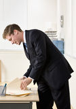 Businessman looking through file folders Stock Photo
