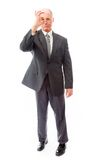Businessman looking through finger's hole. Businessman shot in studio isolated on a white background Royalty Free Stock Image