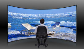 Businessman looking at  frozen sea. Businessman sitting in movie house and looking at  frozen sea Royalty Free Stock Images